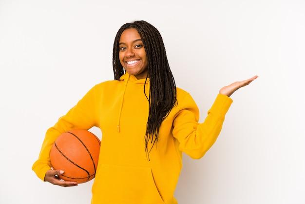 Jeune femme afro-américaine jouant au basket-ball isolé montrant un espace de copie sur une paume et tenant une autre main sur la taille.