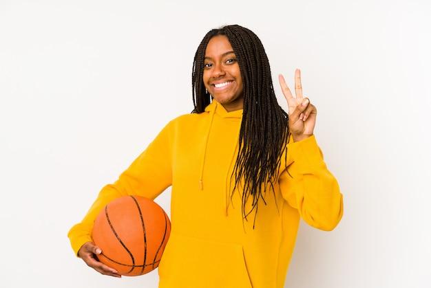 Jeune femme afro-américaine jouant au basket-ball isolé montrant le numéro deux avec les doigts.