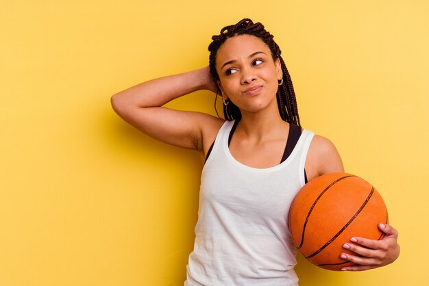 Jeune femme afro-américaine jouant au basket-ball isolé sur un mur jaune touchant l'arrière de la tête, en pensant et en faisant un choix.
