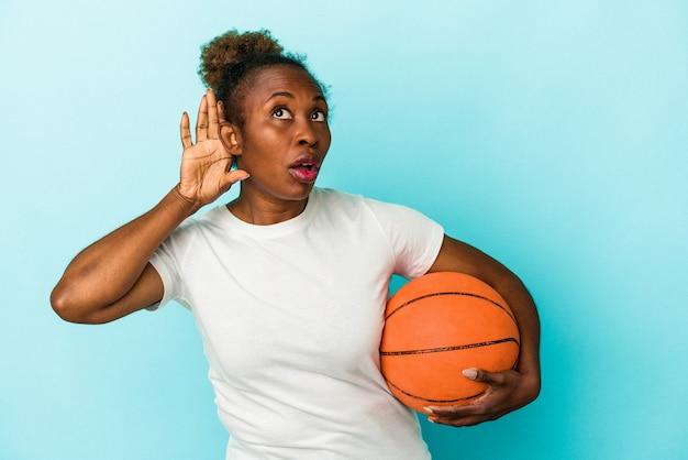 Jeune femme afro-américaine jouant au basket-ball isolée sur fond bleu essayant d'écouter un potin.