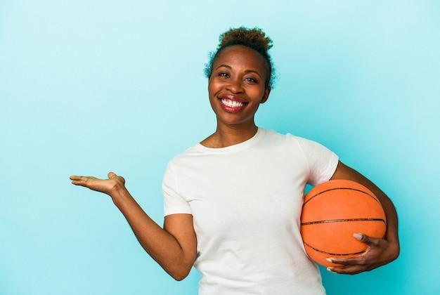 Jeune femme afro-américaine jouant au basket-ball isolée sur fond bleu montrant un espace de copie sur une paume et tenant une autre main sur la taille.