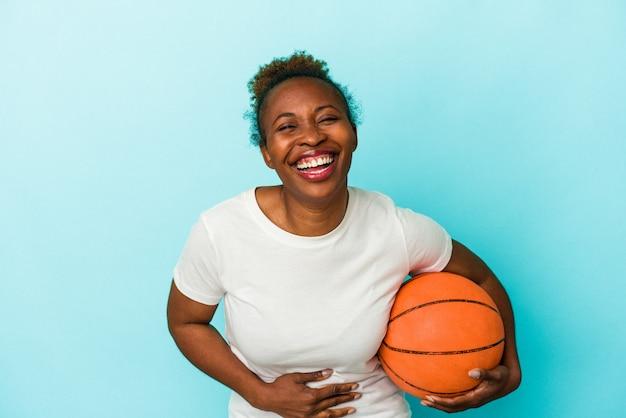 Jeune femme afro-américaine jouant au basket-ball isolée sur fond bleu en riant et en s'amusant.
