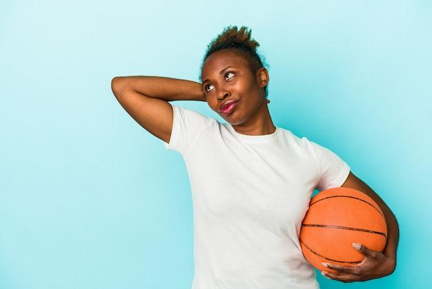 Jeune femme afro-américaine jouant au basket-ball isolée sur fond bleu touchant l'arrière de la tête, pensant et faisant un choix.