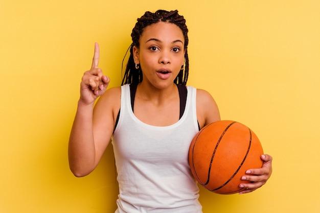 Jeune femme afro-américaine jouant au basket isolé sur un mur jaune ayant une idée, un concept d'inspiration.