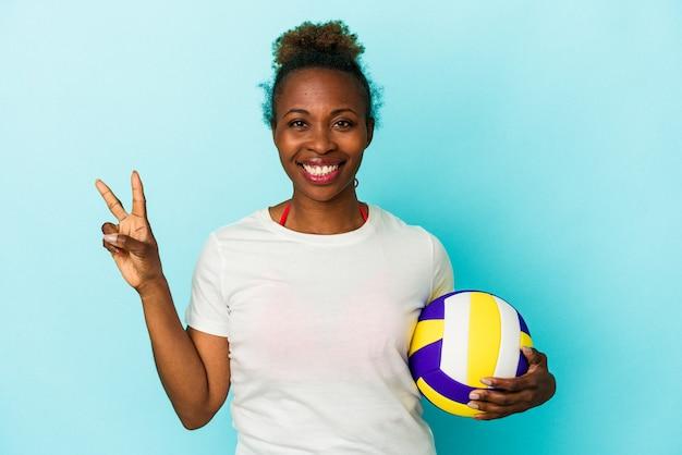 Jeune femme afro-américaine jouant au volley-ball isolé sur fond bleu montrant le numéro deux avec les doigts.