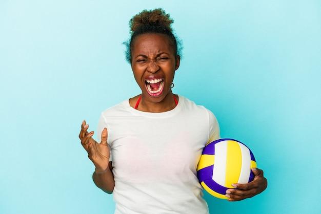 Jeune femme afro-américaine jouant au volley-ball isolée sur fond bleu criant très en colère et agressive.