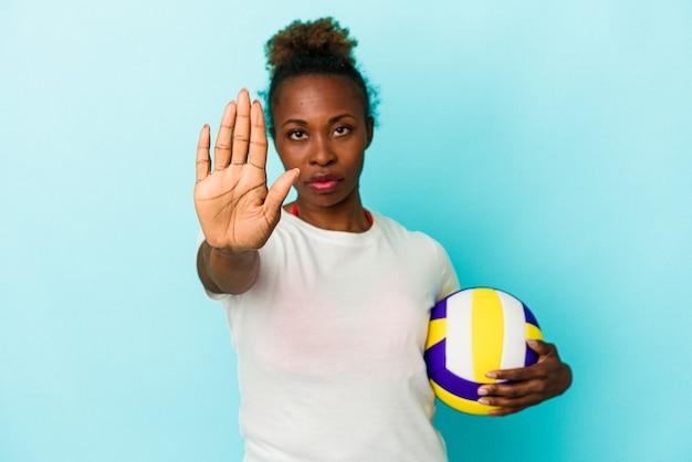 Jeune femme afro-américaine jouant au volley-ball isolée sur fond bleu, debout avec la main tendue montrant un panneau d'arrêt, vous empêchant.