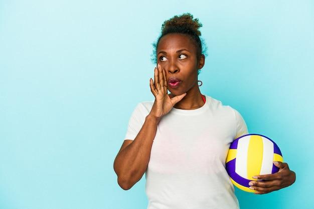 Jeune femme afro-américaine jouant au volley-ball isolée sur fond bleu dit une nouvelle secrète de freinage à chaud et regarde de côté