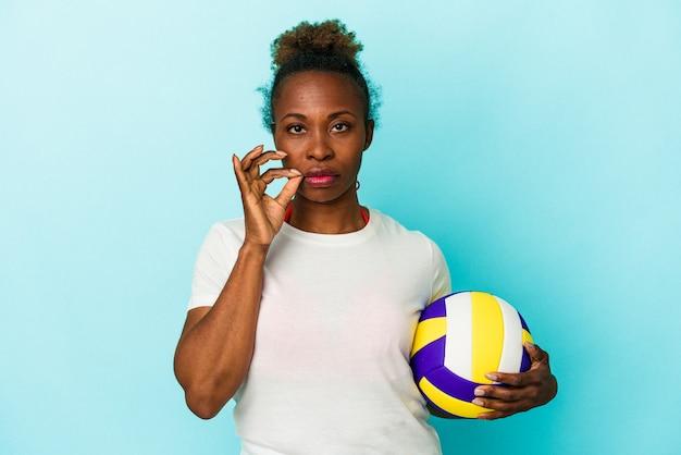 Jeune femme afro-américaine jouant au volley-ball isolée sur fond bleu avec les doigts sur les lèvres gardant un secret.