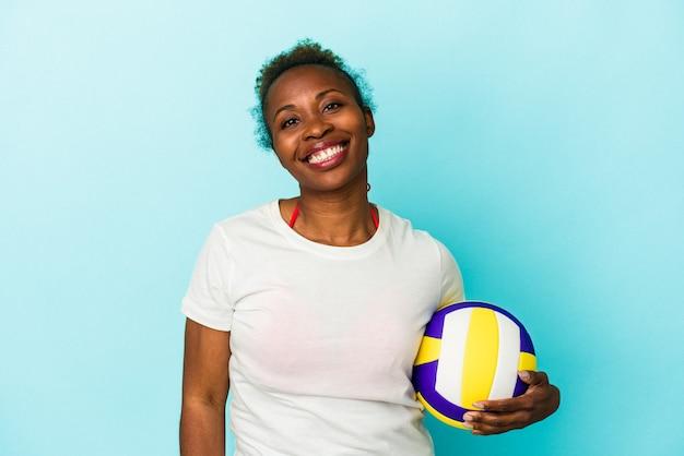 Jeune femme afro-américaine jouant au volley-ball isolée sur fond bleu heureuse, souriante et joyeuse.