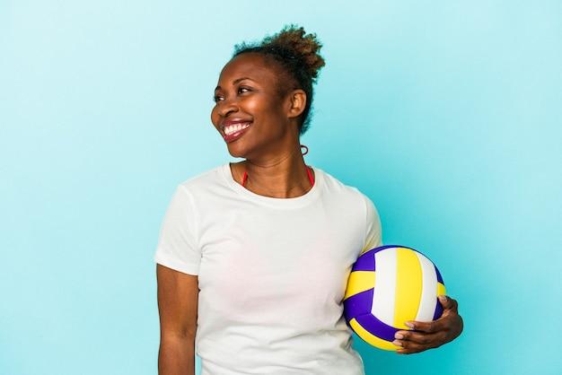 Jeune femme afro-américaine jouant au volley-ball isolée sur fond bleu regarde de côté souriante, gaie et agréable.