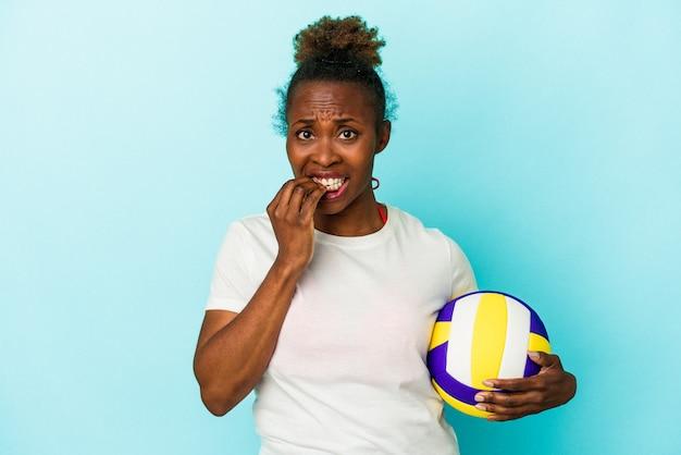 Jeune femme afro-américaine jouant au volley-ball isolée sur fond bleu se rongeant les ongles, nerveuse et très anxieuse.