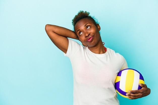 Jeune femme afro-américaine jouant au volley-ball isolée sur fond bleu touchant l'arrière de la tête, pensant et faisant un choix.