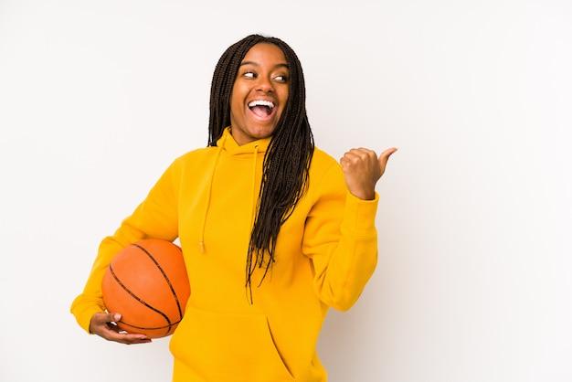 Jeune femme afro-américaine jouant des points isolés de basket-ball avec le doigt de pouce loin, riant et insouciant.