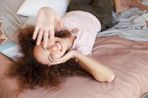 Une jeune femme afro-américaine joyeuse profite de la journée ensoleillée à la maison, passe la journée libre et se repose à la maison, allongée sur le lit et souriant largement et touche la joue.