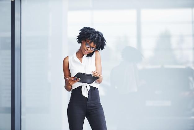 Jeune femme afro-américaine à lunettes se tient à l'intérieur et a un appel d'affaires.