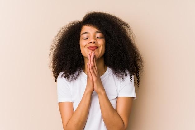 Jeune femme afro-américaine, main dans la main, priez près de la bouche, se sent confiant.