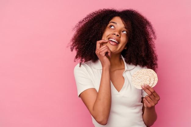 Jeune femme afro-américaine mangeant un gâteaux de riz isolé sur fond rose détendu penser à quelque chose en regardant un espace de copie.