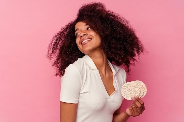 Jeune femme afro-américaine mangeant un gâteaux de riz isolé sur fond rose regarde de côté souriant, gai et agréable.