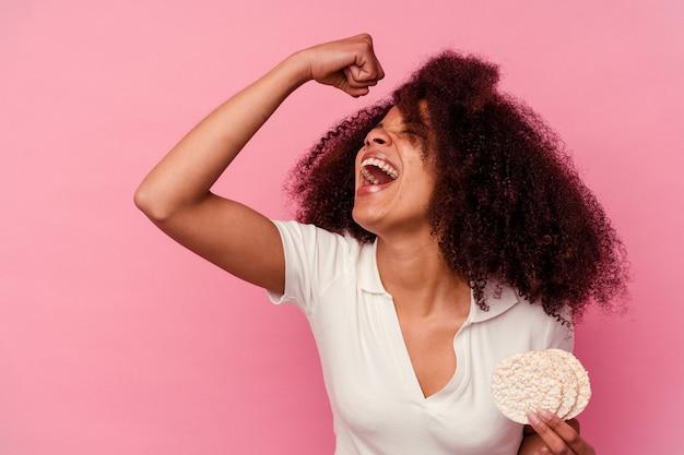 Jeune femme afro-américaine mangeant des gâteaux de riz isolés sur fond rose levant le poing après une victoire, concept gagnant.