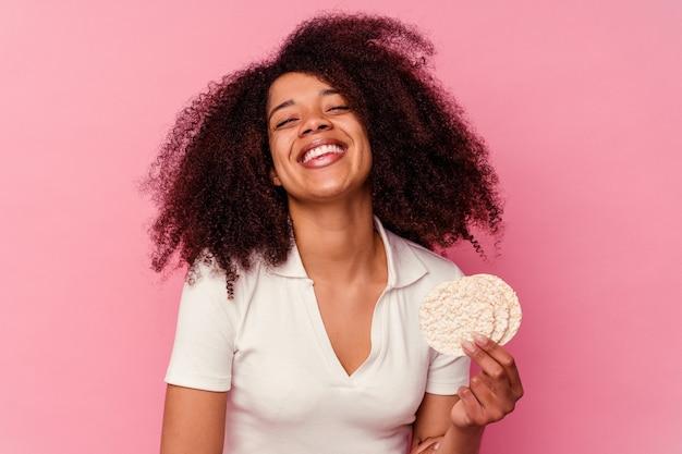 Jeune femme afro-américaine mangeant des gâteaux de riz isolés sur fond rose en riant et en s'amusant.