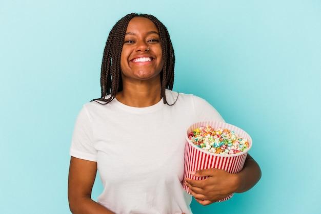 Jeune femme afro-américaine mangeant des pop corns isolés sur fond bleu en riant et en s'amusant.