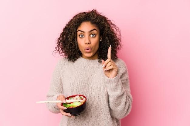 Jeune femme afro-américaine, manger des nouilles ayant une excellente idée, concept de créativité.