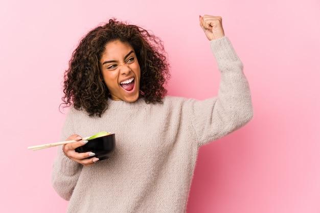 Jeune femme afro-américaine, manger des nouilles levant le poing après une victoire, concept gagnant.