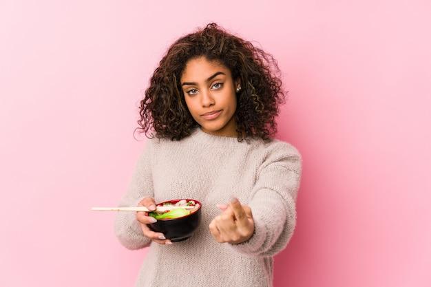 Jeune femme afro-américaine, manger des nouilles pointant du doigt vers vous comme si vous vous invitiez à vous rapprocher.