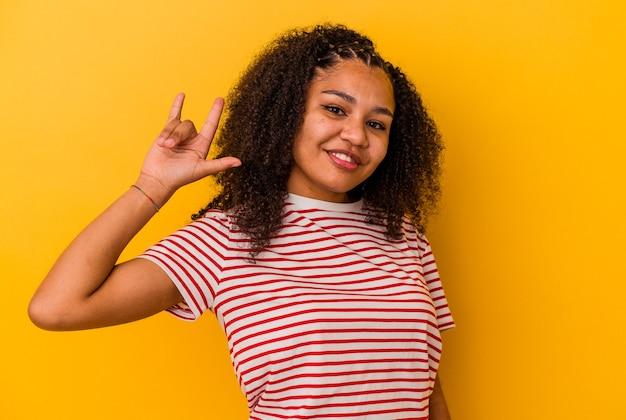 Jeune femme afro-américaine montrant un geste de cornes comme un concept de révolution.