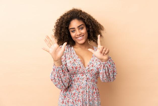 Jeune femme afro-américaine sur mur beige comptant sept avec les doigts