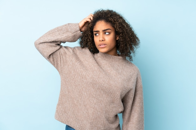 Jeune femme afro-américaine sur mur bleu ayant des doutes en se grattant la tête