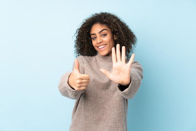 Jeune femme afro-américaine sur mur bleu comptant six avec les doigts