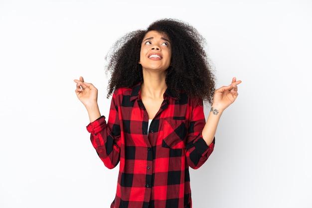 Jeune femme afro-américaine sur un mur isolé avec les doigts traversant et souhaitant le meilleur
