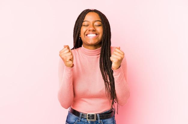 Jeune femme afro-américaine sur un mur rose levant le poing, se sentant heureuse et réussie.