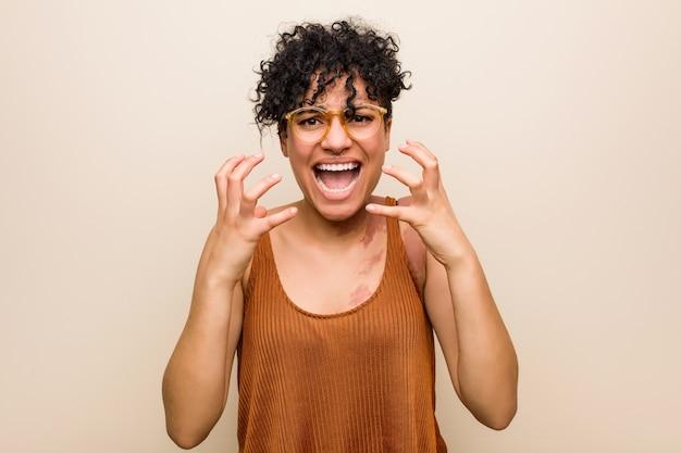 Jeune femme afro-américaine avec la naissance de la peau marque contrariée crier avec les mains tendues.