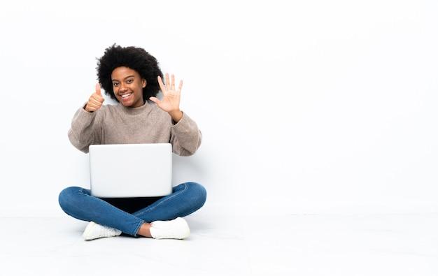 Jeune femme afro-américaine avec un ordinateur portable assis sur le sol en comptant six avec les doigts