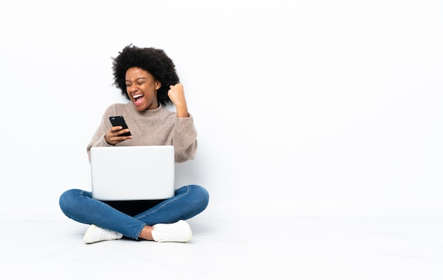 Jeune femme afro-américaine avec un ordinateur portable assis sur le sol avec téléphone en position de victoire
