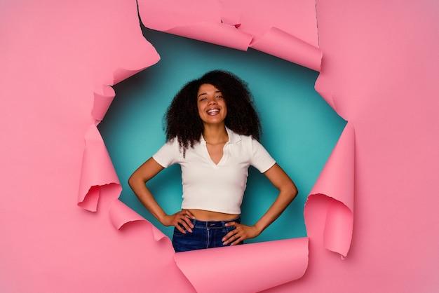 Jeune femme afro-américaine en papier déchiré isolé sur bleu confiant en gardant les mains sur les hanches.