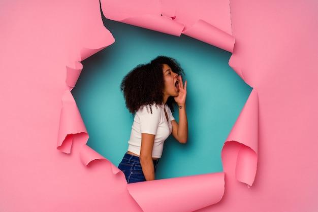Jeune femme afro-américaine en papier déchiré isolé sur bleu criant et tenant la paume près de la bouche ouverte.