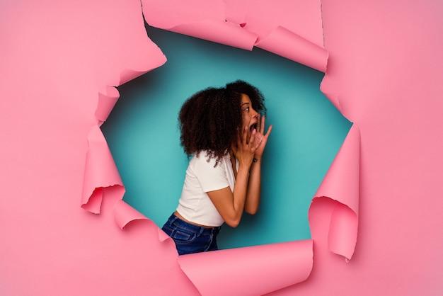 Jeune femme afro-américaine en papier déchiré isolé sur bleu crie fort, garde les yeux ouverts et les mains tendues.