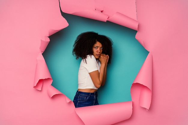 Jeune femme afro-américaine en papier déchiré isolé sur bleu effrayé et effrayé.