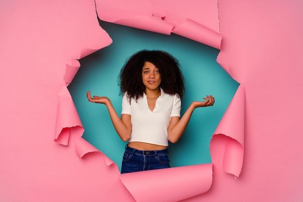Jeune femme afro-américaine en papier déchiré isolé sur bleu, haussant les épaules confuses et douteuses pour tenir un espace de copie.
