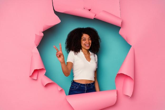 Jeune femme afro-américaine en papier déchiré isolé sur bleu joyeux et insouciant montrant un symbole de paix avec les doigts.