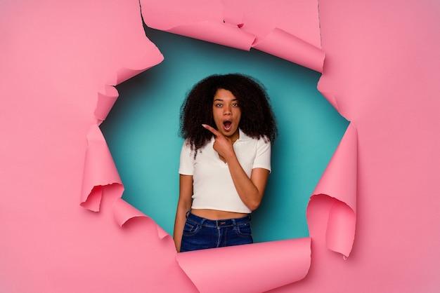 Jeune femme afro-américaine en papier déchiré isolé sur bleu pointant vers le côté