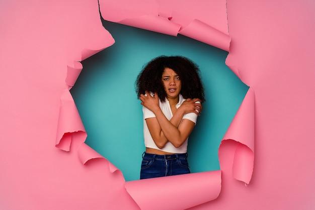 Jeune femme afro-américaine en papier déchiré isolé sur bleu qui fait froid en raison d'une basse température ou d'une maladie.
