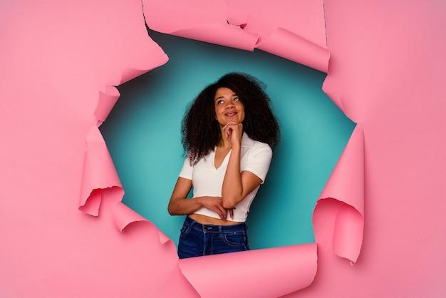 Jeune femme afro-américaine en papier déchiré isolé sur bleu regardant de côté avec une expression douteuse et sceptique.