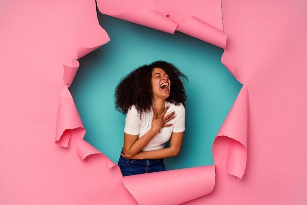 Jeune femme afro-américaine en papier déchiré isolé sur bleu rit joyeusement et s'amuse à garder les mains sur le ventre.