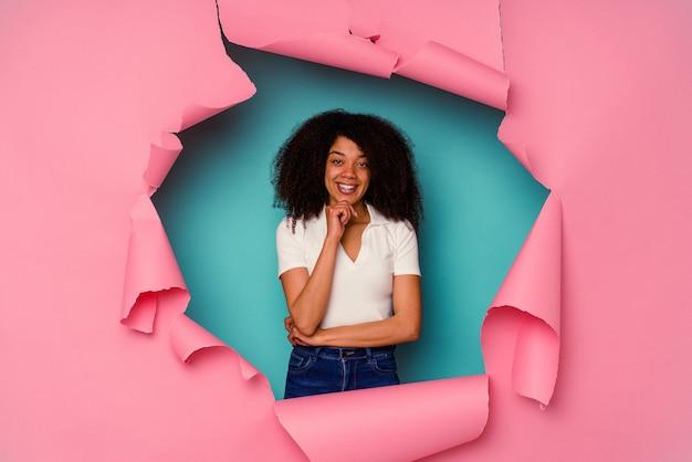 Jeune femme afro-américaine en papier déchiré isolé sur bleu souriant heureux et confiant, touchant le menton avec la main.