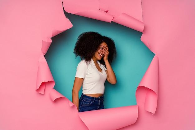 Jeune femme afro-américaine en papier déchiré isolé sur fond bleu clignote à l'appareil photo à travers les doigts, embarrassé couvrant le visage.